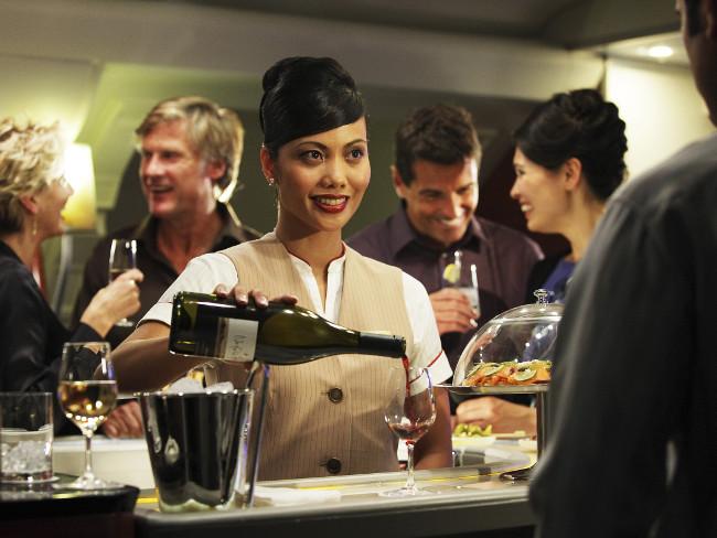 Una azafata sirve vino en el Onboard Lounge de los A380 de Emirates.