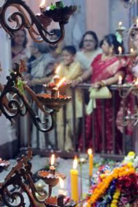 Fieles detrás de velas en Puja