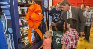 El alcalde de Fort Lauderdale, Jack Seiler, y el director Compensación, Beneficios y Responsabilidad Social Corporativa en la aerolínea JetBlue, Harry Spencer (detrás) con unos niños delante de una de las máquinas expendedoras de libros.