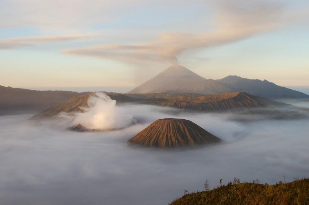 Entre nubes, humo y azufre, asoman el Monte Bromo  y al fondo, el Monte Semeru. Semeru es la montaña más alta de Java. Y es un volcán que lleva activo desde 1967 con pequeñas erupciones de aprox. 20 minutos de duración.