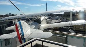 """Réplica del biplano del """"Pájaro blanco"""" de los años veinte apuntando a la torre Eiffel"""