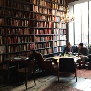 Tomar una taza de té y un croissant entre libros o carteles de películas en Le Cinéma Café & Le Used Book Café de Merci