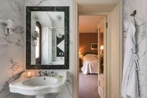 Elegantes baños de mármol de Carrara, grises y blancos, y mobiliario retro
