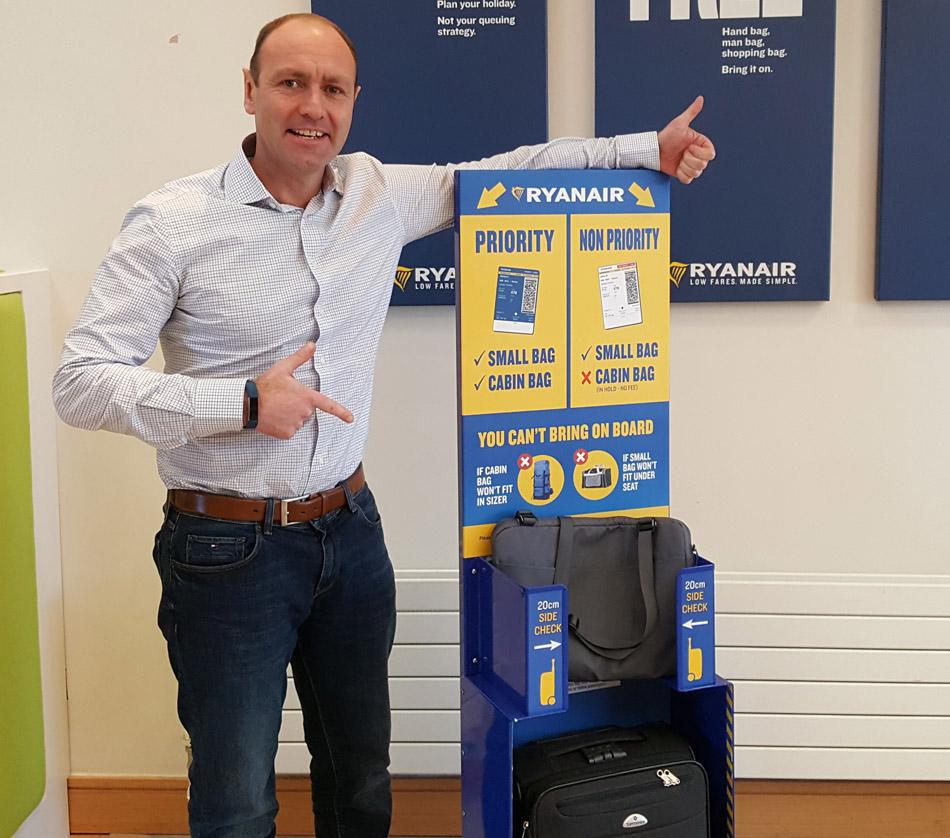 Kenny Jacobs, director de Marketing de Ryanair, junto a un medidores de equipaje que se colocarán en cada puerta de embarque