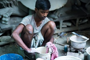 En el barrio de Kurmatuli: un joven mezclando pintura con la mano.