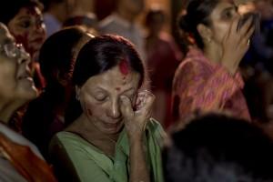Una mujer se seca las lágrimas mientras ve como una diosa Durga es trasladada al río para su inmersión.