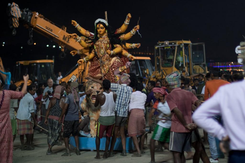 Un grupo de porteadores acerca una representación de la Diosa hasta la orilla del río Hugli para proceder a su inmersión.