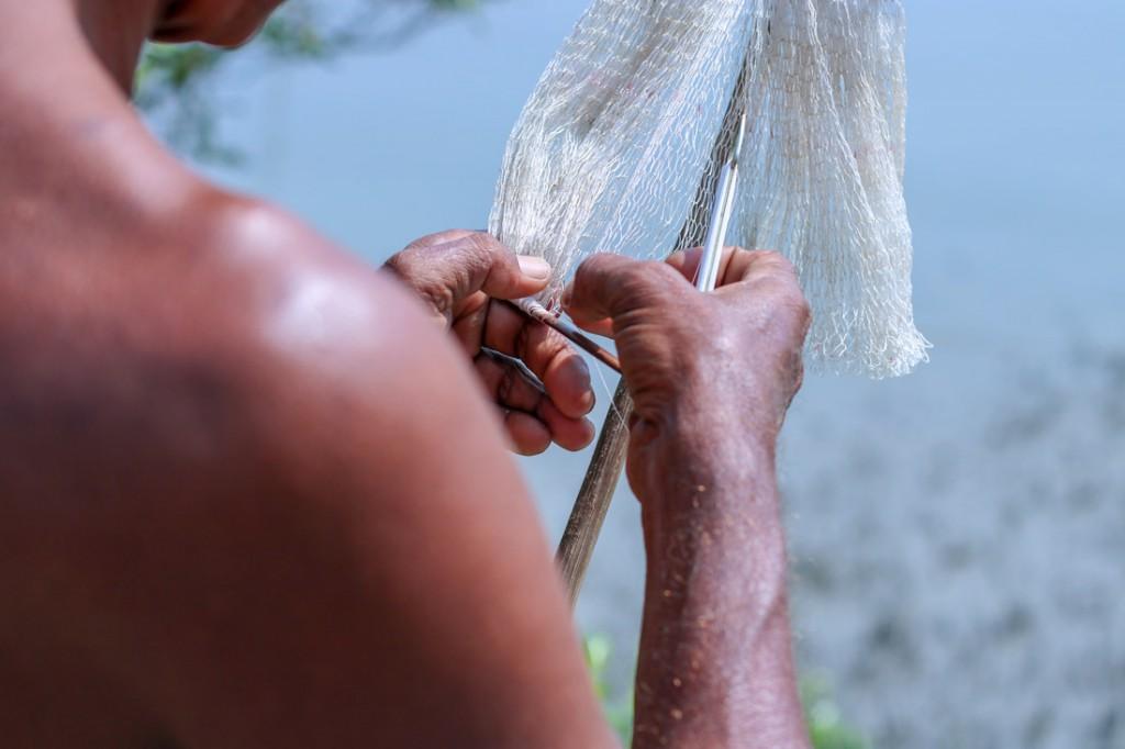Un hombre teje a mano una red de pesca: el tigre de Bengala, hábil nadador, es una gran amenaza para los pescadores.