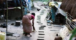 Una mujer barre la entrada a de su casa en una pequeña aldea del Sundarbans.