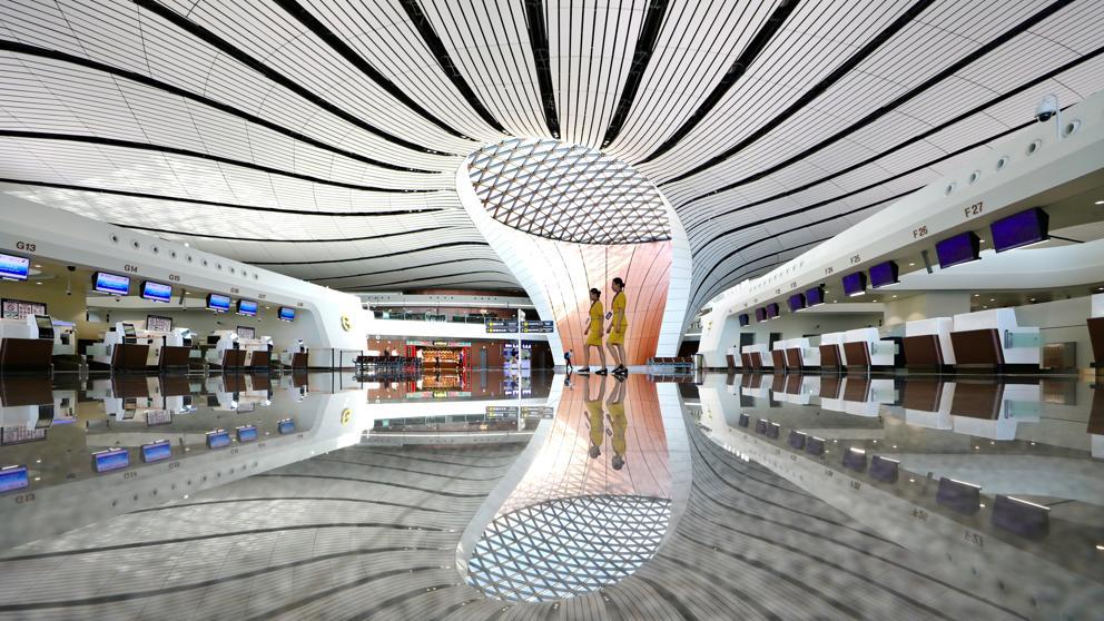 Dos miembros del personal caminan por la sala de check-in del recién inaugurado Aeropuerto Internacional de Daxing en Pekín. Foto: China Stringer Network / Reuters