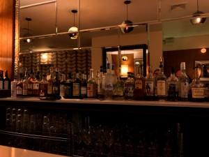 Iluminación tenue de lámparas vintage, mesas de latón, paredes cubiertas con papel pintado y espejos antiguos dan la personalidad setentera a Ruby's.