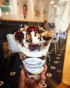 Helado de vainilla con nueces, cerezas, crema batida y salsa de chocolate de Sugar Hill Creamery.