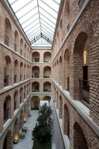 Tres patios interiores configurados por grandes arquerías.